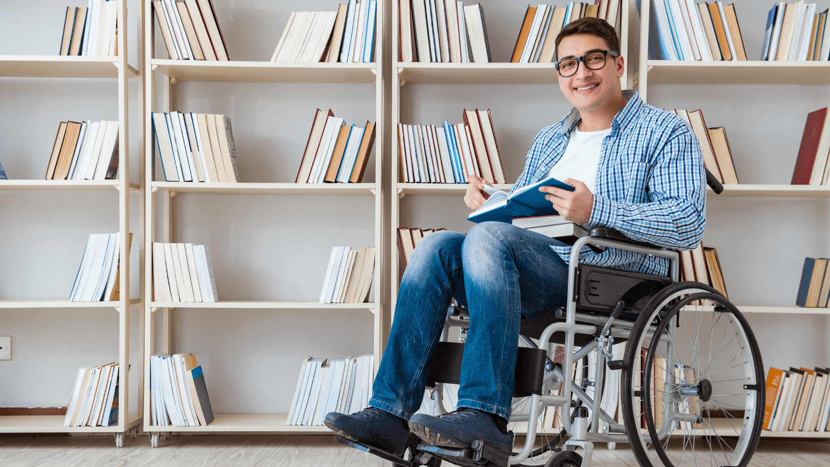 Person in wheelchair by bookshelf.