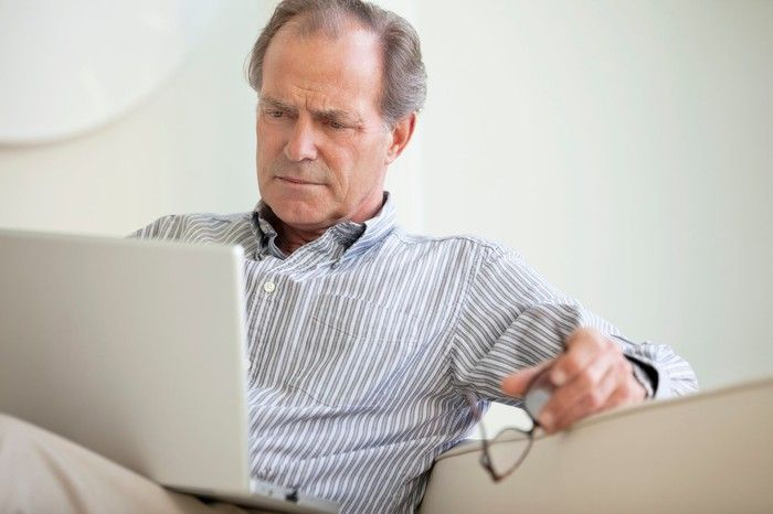 A man sitting on his couch using a laptop