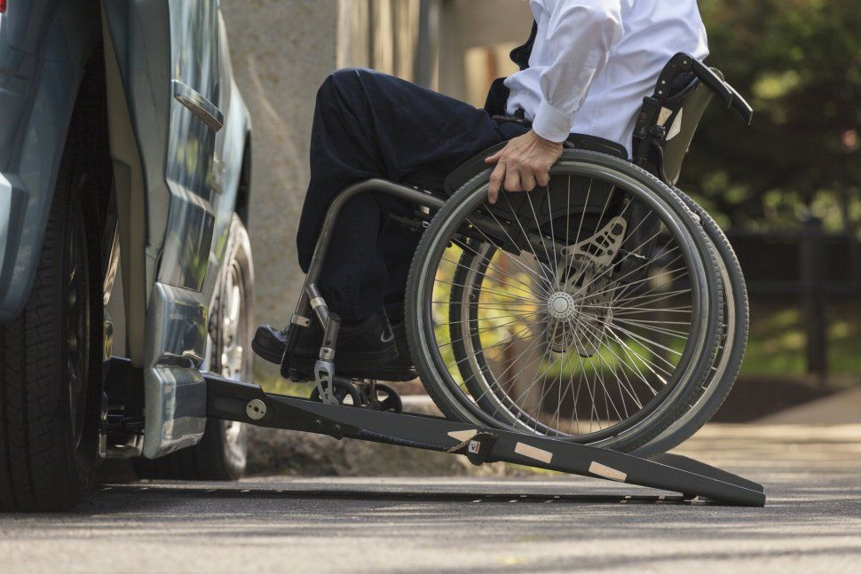 A man going down the sidewalk in a wheelchair