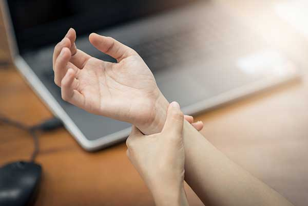 A person holding their wrist in pain due to carpal tunnel