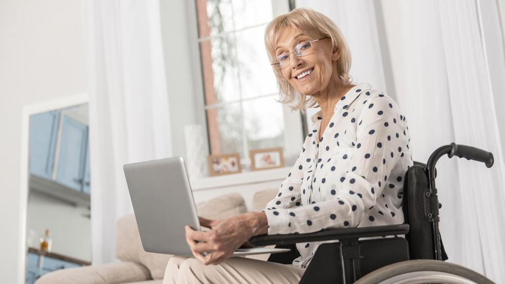 A happy woman using a laptop while sitting in her wheelchair