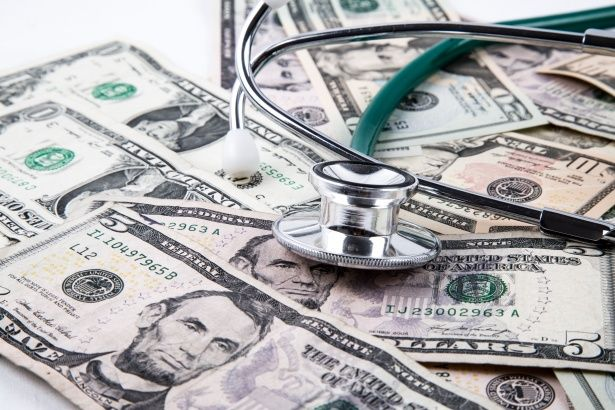 A pile of money with a stethoscope laying on top of it