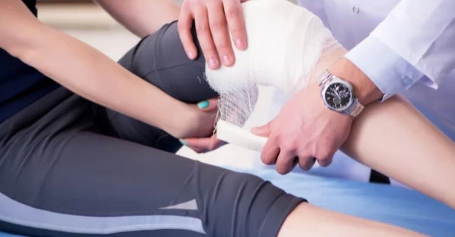 A doctor wrapping up a girls knee in a bandage