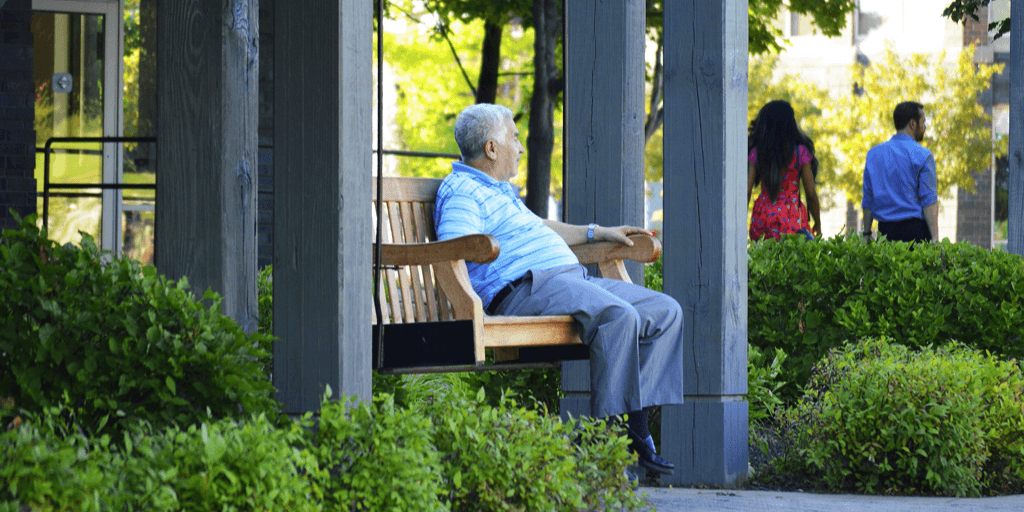 middle aged man sitting on a bench.