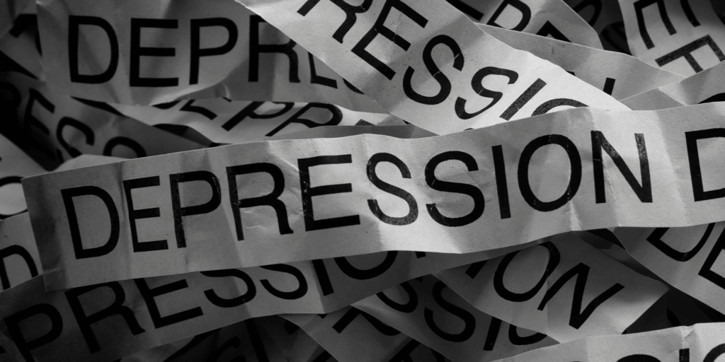 The word depression on many pieces of paper in a pile together.