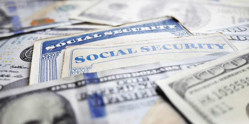 social security cards surrounded by 100 dollar bills.